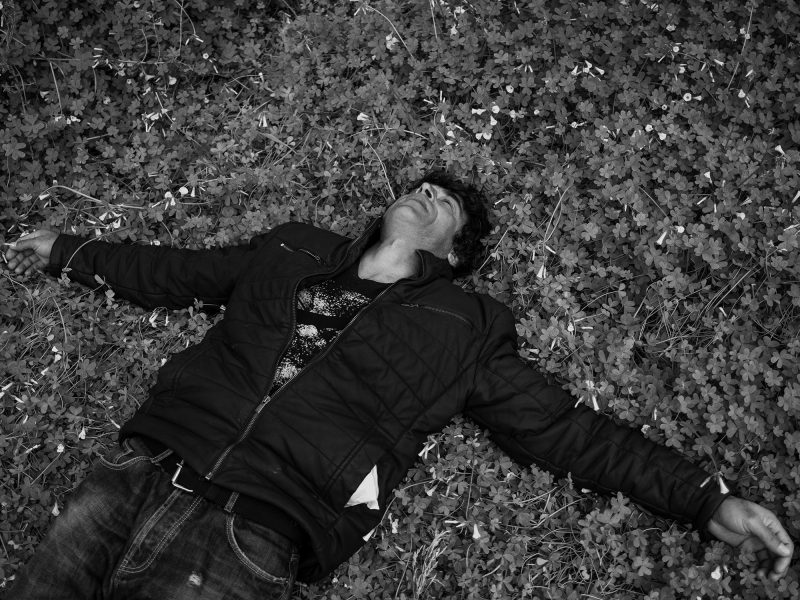 A man from Afghanistan lies down in a land. Lesvos, Greece, The Island, 2020