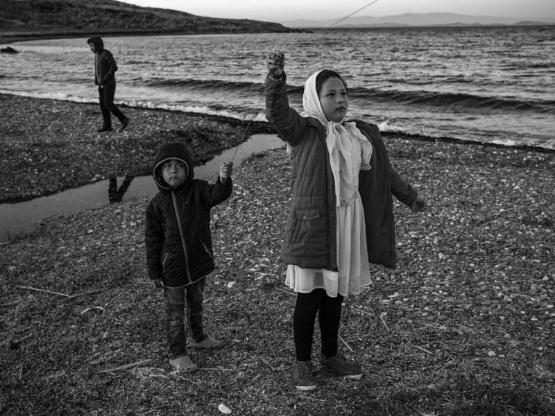 Two Afghan children fly a kite together. Lesvos, Greece, The Island, 2020